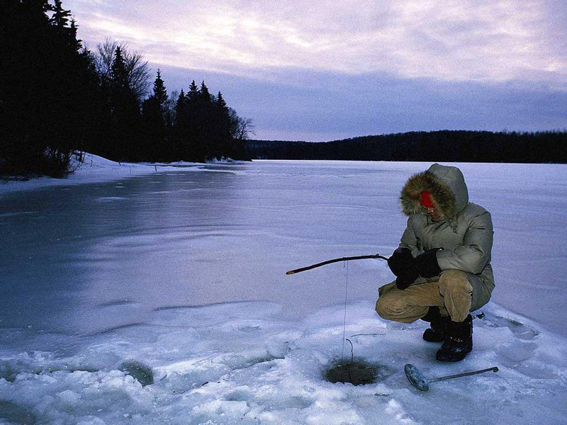 Person kneeling ice fishing